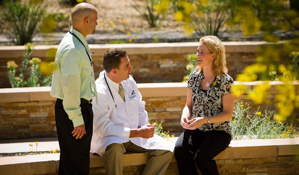 Three Midwestern University faculty members conversing outside